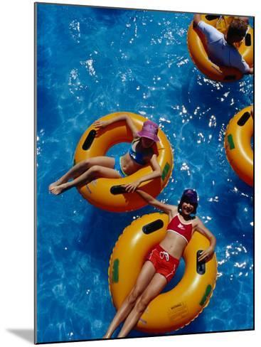 Young Girls Floating in Rubber Rings in Swimming Pool, Gold Coast, Australia-Richard I'Anson-Mounted Photographic Print