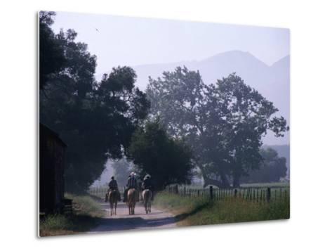 Cattlemen Riding Horses along a Road at Rancho Sisquoc, Santa Barbara, California, USA-Brent Winebrenner-Metal Print