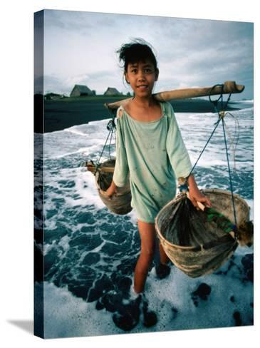 A Girl Gathers Salt Water in Lontar Leaf Buckets for Salt Making, Kusamba, Indonesia-Adams Gregory-Stretched Canvas Print
