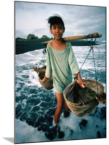 A Girl Gathers Salt Water in Lontar Leaf Buckets for Salt Making, Kusamba, Indonesia-Adams Gregory-Mounted Photographic Print