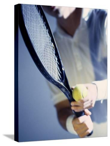 Close-up of a Young Man Holding a Tennis Racket and a Tennis Ball--Stretched Canvas Print