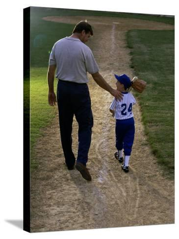 Rear View of a Man Walking with His Son at a Playing Field--Stretched Canvas Print