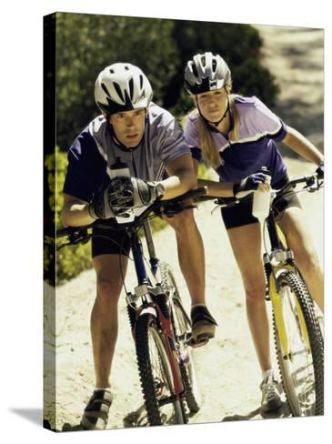 Portrait of a Young Couple Sitting on Bicycles--Stretched Canvas Print