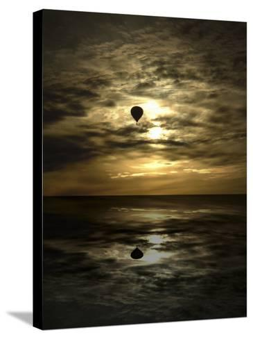 Silhouette of a Hot Air Balloon Over Water--Stretched Canvas Print