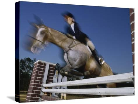 Low Angle View of a Woman Riding a Horse Over a Hurdle--Stretched Canvas Print