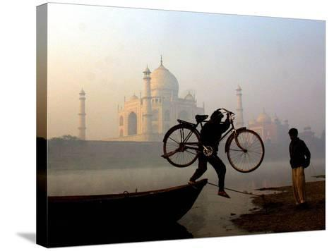 An Unidentified Cyclist Gets Down with His Cycle against the Backdrop of the Taj Mahal--Stretched Canvas Print