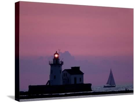 A Sailboat Slips Past a Lighthouse as the Sunset Comes to Lake Erie off the Coast of Cleveland--Stretched Canvas Print