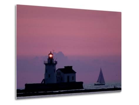 A Sailboat Slips Past a Lighthouse as the Sunset Comes to Lake Erie off the Coast of Cleveland--Metal Print