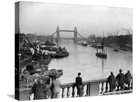 Pedestrians on London Bridge Watch Boats and Barges Being Unloaded--Stretched Canvas Print