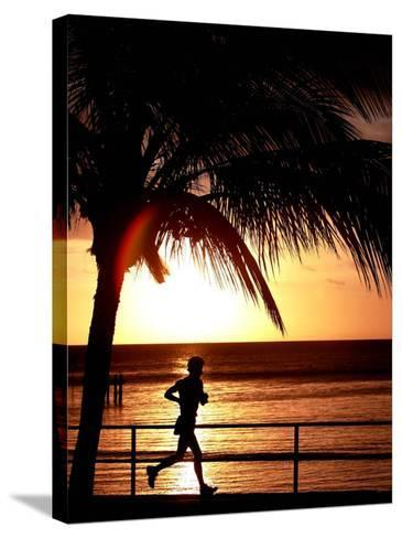 A Afternoon Runner Passes Under a Palm Tree as the Sun Sets Behind--Stretched Canvas Print