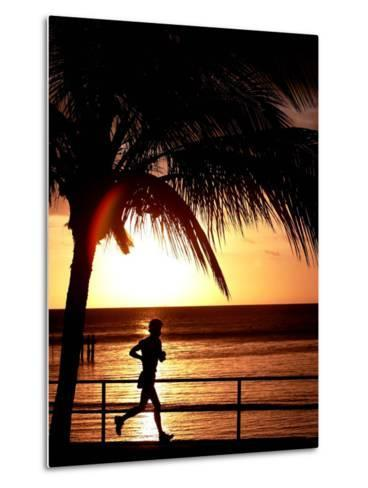 A Afternoon Runner Passes Under a Palm Tree as the Sun Sets Behind--Metal Print