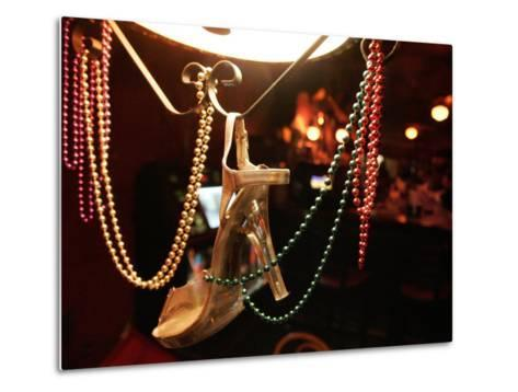 A Woman's High Heeled Shoe Hangs with Some Mardi Gras Beads--Metal Print