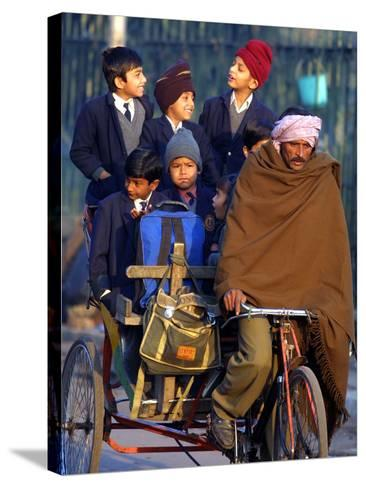 Indian Children Ride to School on the Back of a Cycle Rickshaw--Stretched Canvas Print
