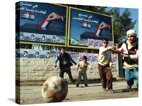 """Iraqi Boys Play Soccer Below the Poster Reading """"To Grant Iraqi Children Better Iraq""""--Stretched Canvas Print"""