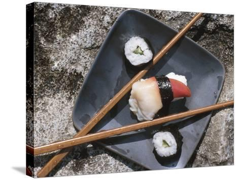 Sushi and Chopsticks Beside Rushing Water--Stretched Canvas Print