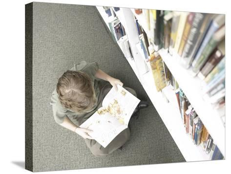 Little Boy Reading Book Beside Library Shelf--Stretched Canvas Print