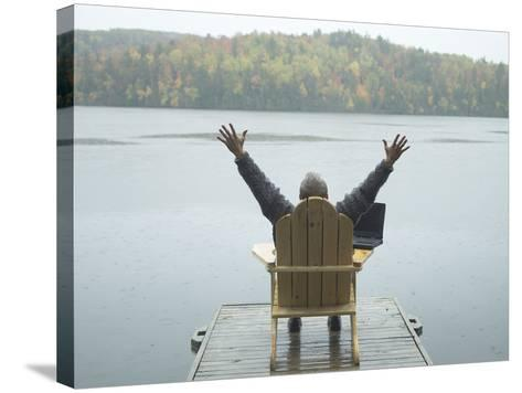 Man Sitting on a Dock with Arms Outstretched--Stretched Canvas Print
