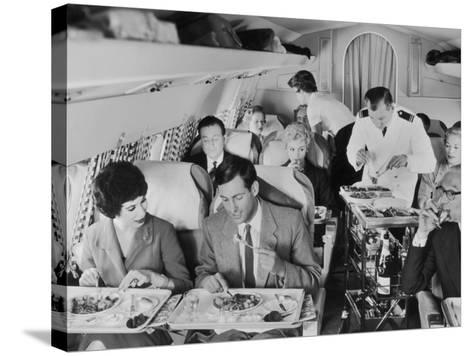 An Airline Steward and Air Hostess Serve a Roast Meal to Flight Passengers--Stretched Canvas Print