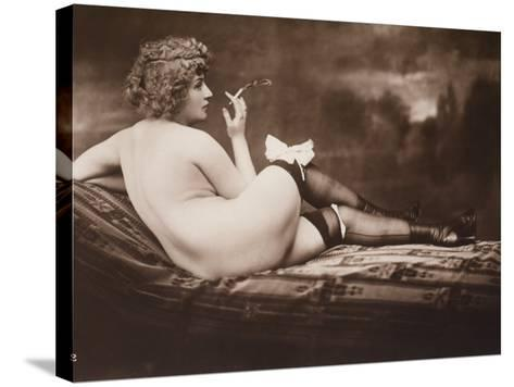 Portrait of a Young Woman Posing Naked, with Her Back Turned, as She Smokes a Cigarette--Stretched Canvas Print