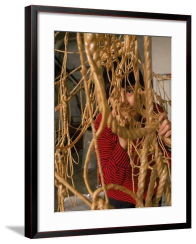 Eva Hesse Peering Through Her Sculpture of Rubber Dipped String and Rope-Henry Groskinsky-Framed Art Print