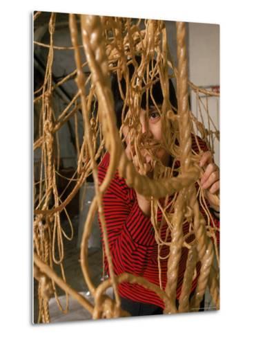 Eva Hesse Peering Through Her Sculpture of Rubber Dipped String and Rope-Henry Groskinsky-Metal Print