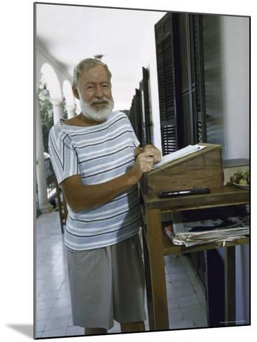 Ernest Hemingway at the Standing Desk on the Balcony of Bill Davis's Home Near Malaga-Loomis Dean-Mounted Premium Photographic Print