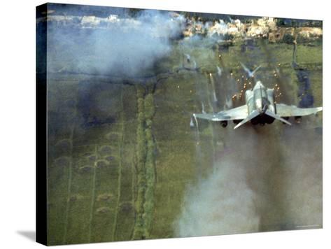 American F4C Phantom Jet Firing Rockets into Viet Cong Stronghold village During the Vietnam War-Larry Burrows-Stretched Canvas Print