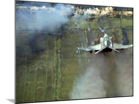 American F4C Phantom Jet Firing Rockets into Viet Cong Stronghold village During the Vietnam War-Larry Burrows-Mounted Photographic Print