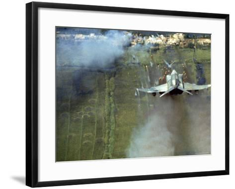 American F4C Phantom Jet Firing Rockets into Viet Cong Stronghold village During the Vietnam War-Larry Burrows-Framed Art Print