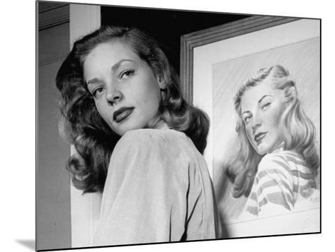 Actress Lauren Bacall Posing in Front of Portrait Drawing of Herself in Suite at the Gotham Hotel-Nina Leen-Mounted Premium Photographic Print