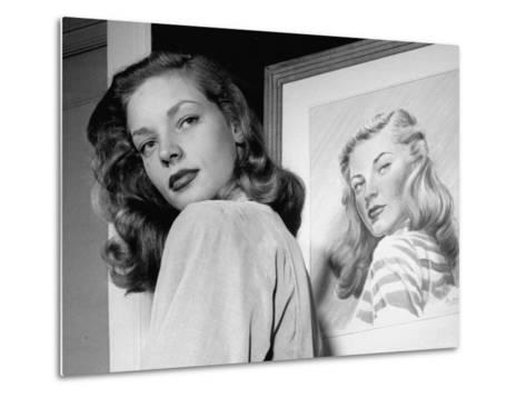 Actress Lauren Bacall Posing in Front of Portrait Drawing of Herself in Suite at the Gotham Hotel-Nina Leen-Metal Print