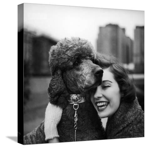 Woman Profiling a Big Smile While Adoring Her Poodle Wearing Large Swiss Watch on Dog Collar-Yale Joel-Stretched Canvas Print
