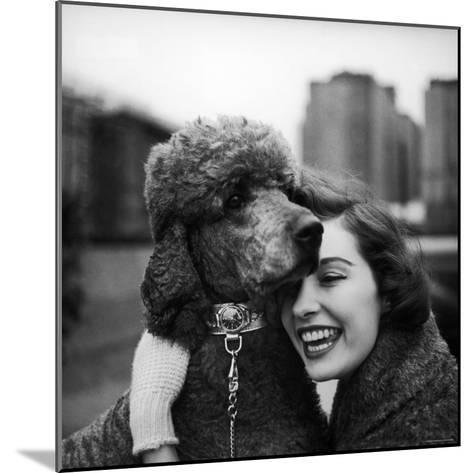 Woman Profiling a Big Smile While Adoring Her Poodle Wearing Large Swiss Watch on Dog Collar-Yale Joel-Mounted Photographic Print