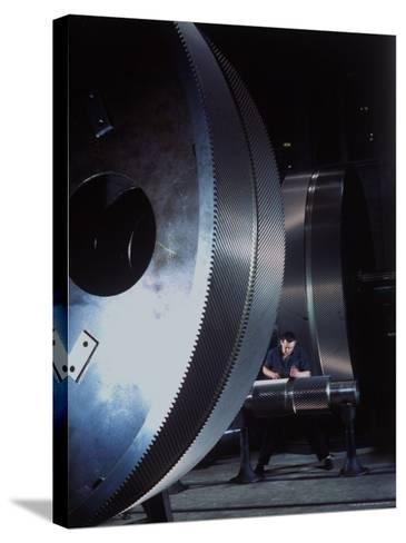 Man Dwarfed by Gigantic Gears He is Working on for the Navy, at General Electric Plant in US-Dmitri Kessel-Stretched Canvas Print