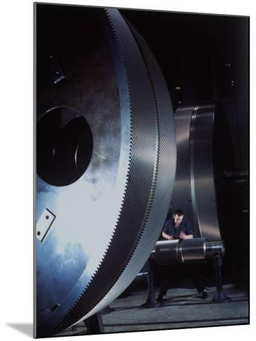 Man Dwarfed by Gigantic Gears He is Working on for the Navy, at General Electric Plant in US-Dmitri Kessel-Mounted Photographic Print