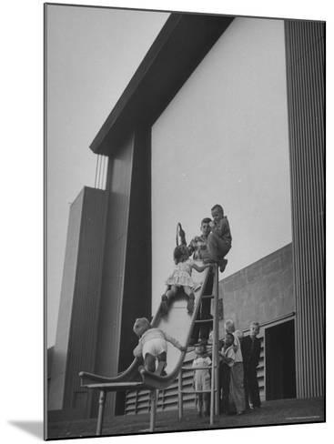 Kids Enjoying Slide in Mini Playground in Front of Rancho Drive-Allan Grant-Mounted Photographic Print