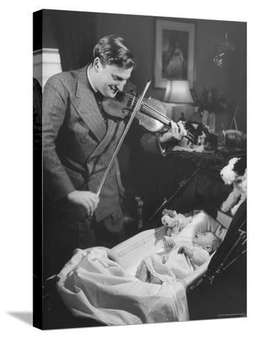 Violinist Yehudi Menuhin, Playing the Violin for His New Baby Daughter in Hotel Room-Hansel Mieth-Stretched Canvas Print