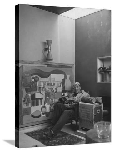 Architect Le Corbusier Sitting in Chair with Book in Hands, Glasses Perched on His Forehead-Nina Leen-Stretched Canvas Print