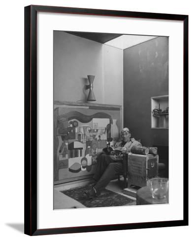 Architect Le Corbusier Sitting in Chair with Book in Hands, Glasses Perched on His Forehead-Nina Leen-Framed Art Print