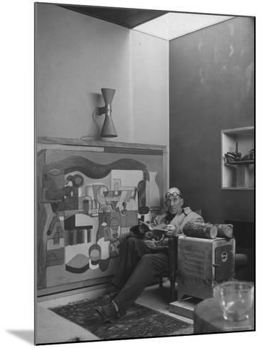 Architect Le Corbusier Sitting in Chair with Book in Hands, Glasses Perched on His Forehead-Nina Leen-Mounted Premium Photographic Print