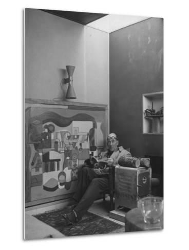 Architect Le Corbusier Sitting in Chair with Book in Hands, Glasses Perched on His Forehead-Nina Leen-Metal Print