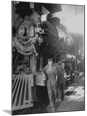 Women Rail Workers Standing at Work on Engine of Train, During WWI at Great Northern Railway--Mounted Photographic Print