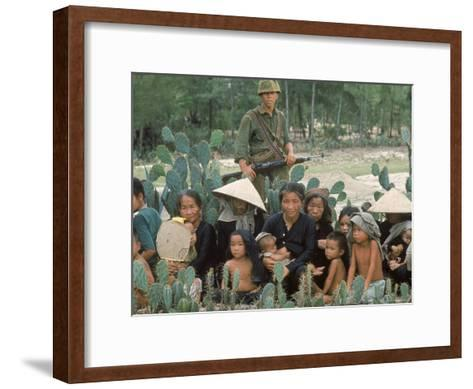 Marine Guarding Mostly Old People and Children Who Are Resting on Their Way to a Refugee Collection-Paul Schutzer-Framed Art Print