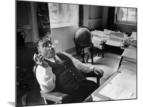Mayor Fiorello LaGuardia Blowing Smoke Rings Sitting at Desk in His Office-William C^ Shrout-Mounted Photographic Print