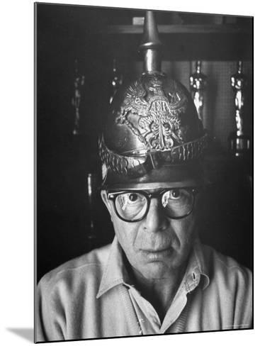 Director Billy Wilder in His Hollywood Office Wearing German Helmet-Gjon Mili-Mounted Premium Photographic Print