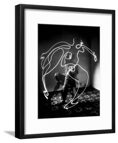 Multiple Exposure of Artist Pablo Picasso Using Flashlight to Make Light Drawing of a Figure-Gjon Mili-Framed Art Print