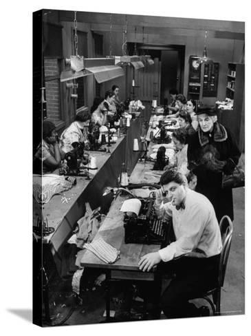 Playwright Paddy Chayefsky Sitting at Typewriter in Garment Factory With Workers on Sewing Machines-Michael Rougier-Stretched Canvas Print