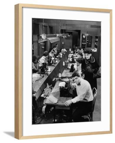 Playwright Paddy Chayefsky Sitting at Typewriter in Garment Factory With Workers on Sewing Machines-Michael Rougier-Framed Art Print