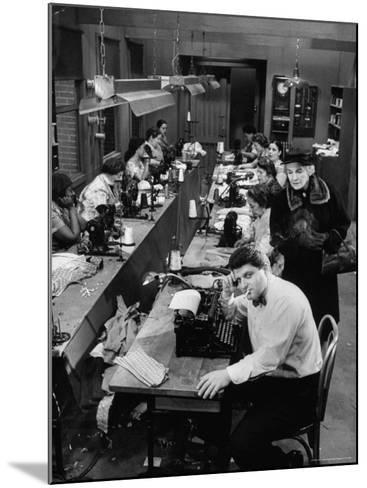 Playwright Paddy Chayefsky Sitting at Typewriter in Garment Factory With Workers on Sewing Machines-Michael Rougier-Mounted Premium Photographic Print