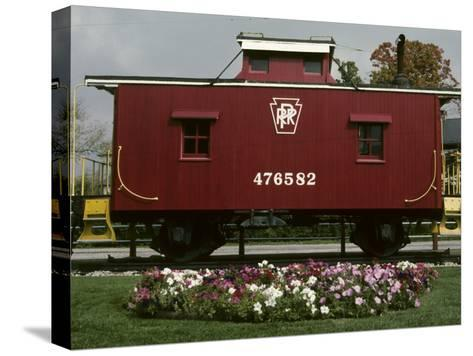 A Bright Red Caboose and a Flower Bed Compete for Vivid Color-Stephen St^ John-Stretched Canvas Print